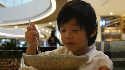 Cute Asian Child Eating Japanese Noodles In A Restaurant