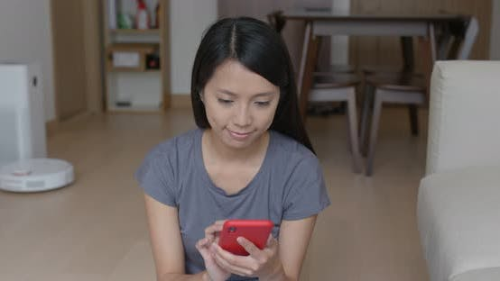 Thumbnail for Woman Use of Mobile Phone to Control Robotic Vacuum Cleaner at Home