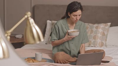 Woman Eating Cereal in Bed Calling on Phone