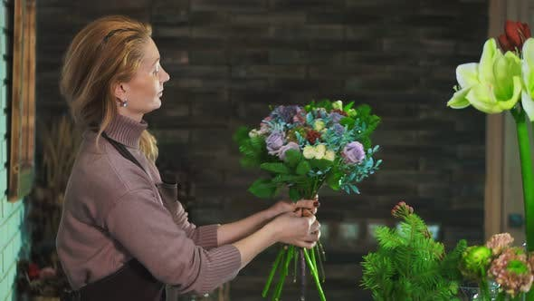 A Woman Florist in an Apron, Standing on the Counter in a Flower Shop, Preparing a Bouquet