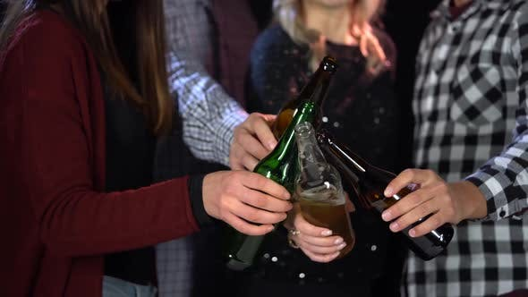 Thumbnail for A Group of Friends Clink Glasses with Beer Bottles