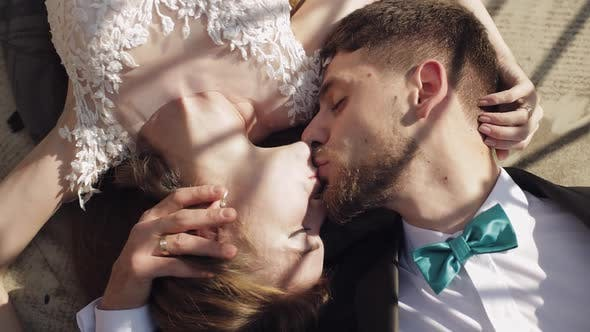 Cover Image for Newlyweds. Caucasian Groom with Bride Lie on the Ground Next To Each Other