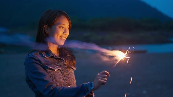 Thumbnail for Woman play sparkler at night