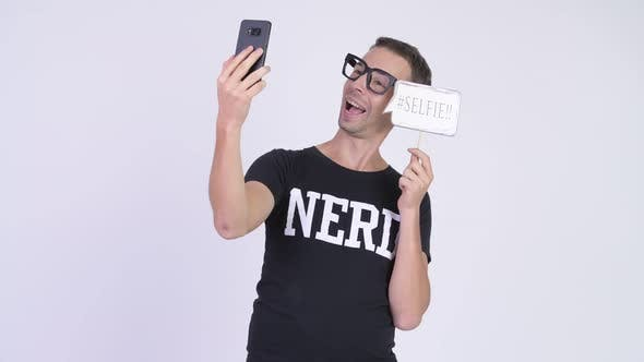 Thumbnail for Studio Shot of Happy Nerd Man Taking Selfie with Paper Sign
