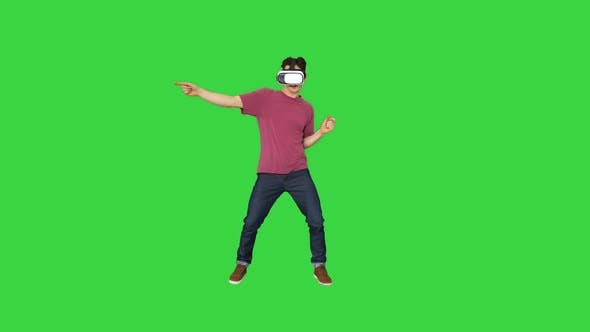 Thumbnail for Advanced Gamer in Casual Outfit Playing Dancing Game in VG Headset on a Green Screen, Chroma Key.