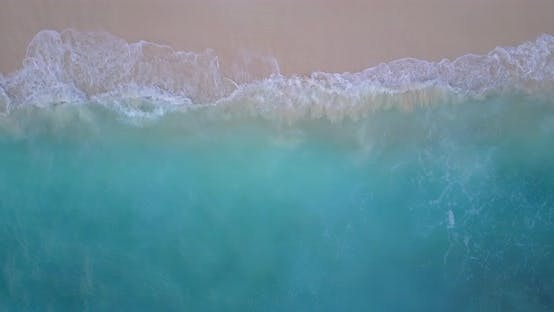 Luxury fly over abstract shot of a sandy white paradise beach and aqua blue ocean background in colo