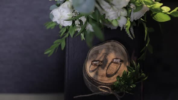 Thumbnail for Beautiful Wedding Rings Lie on Wooden Stand with Wedding Bride's Bouquet