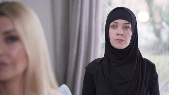 Cover Image for Focus Changes From Modest Muslim Woman in Hijab To Face of Young Modern Caucasian Lady Looking at