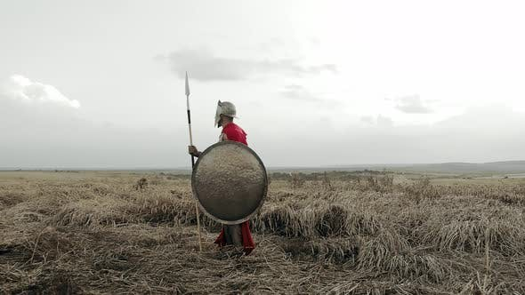 Shirtless Spartan in Armor in Dry Field.