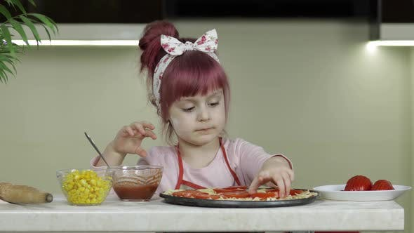Thumbnail for Cooking Pizza. Little Child in Apron Adding Sliced Tomatoes To Dough in Kitchen