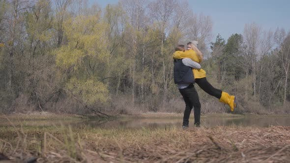 Thumbnail for Blond Woman Running To the Bearded Handsome Man and Jump at His Hugs. Amazing View of River and