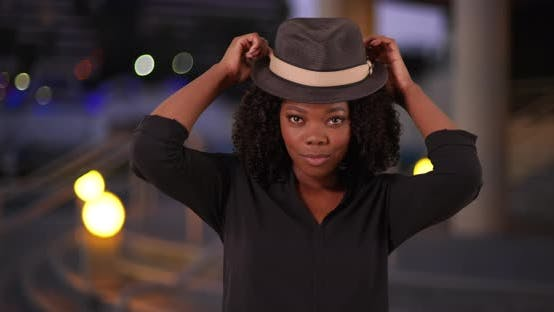 Thumbnail for Attractive black woman in urban setting smoothly puts on stylish hat