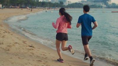 Runners fitness couple running training on the beach.