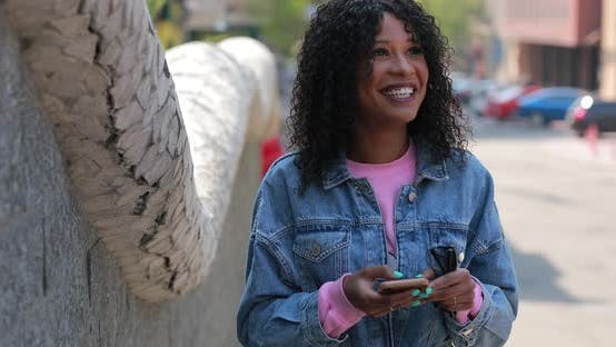 Thumbnail for Multiracial woman reading message in phone with laugh in city