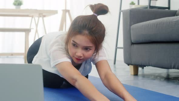 Young lady exercises doing working out and using laptop to watching yoga video tutorial at home