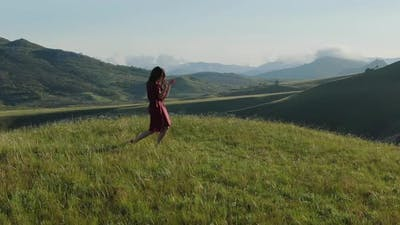 Aerial View and Circular Panorama Around a Young Modern Shaman Woman Who Dances a Dance of Power in