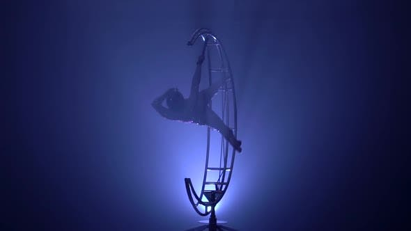 Graceful Gymnast Performs Tricks on a Special Design in a Dark Room. Blue Smoke Background. Slow