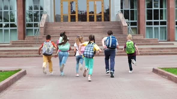 Junior Students with Schoolbags Walk To School Building
