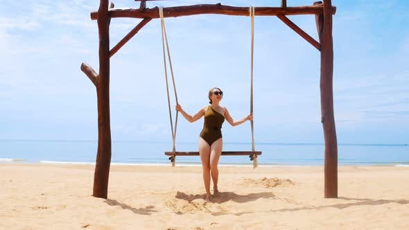 Cover Image for A Young Careless Woman Swinging on a Swings on the Beach
