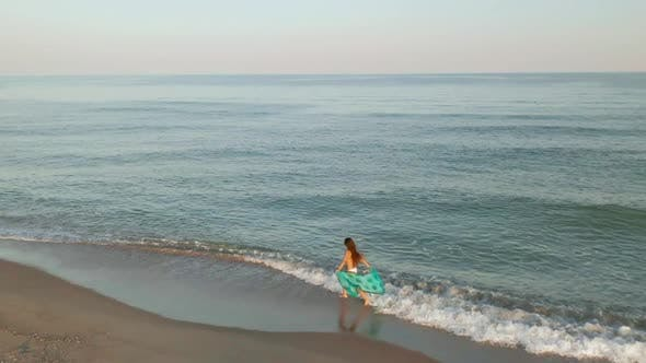 Beautiful Scene of a Woman Walking on Ocean Beach at Sunset