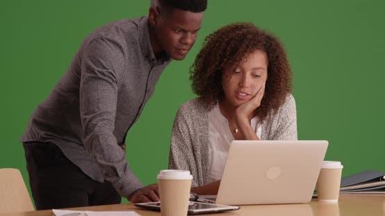 Thumbnail for Millennial coworkers comparing notes using tablets and laptops on green screen