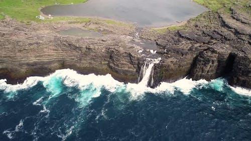 Aerial view of a waterfall near cliff on North Atlantic sea, Faroe island.