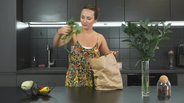 Thumbnail for Portrait of young woman is unpacking products and vegetables from reusable grocery craft paper bag