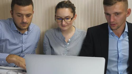 Young Coworkers Examining Financial Reports on Computer at Office