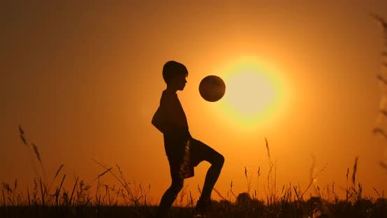 Thumbnail for Little Boy Football Player Silhouette, Boy Juggles a Ball in the Field at Sunset
