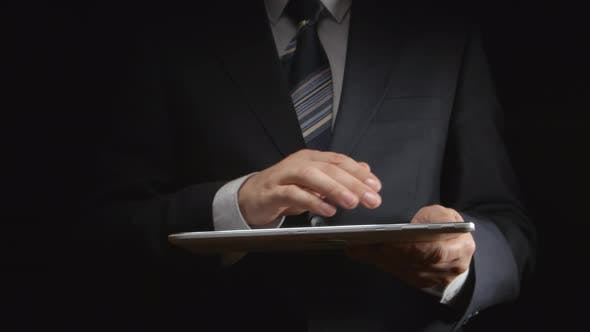 Thumbnail for Businessman holds white tablet PC at hands