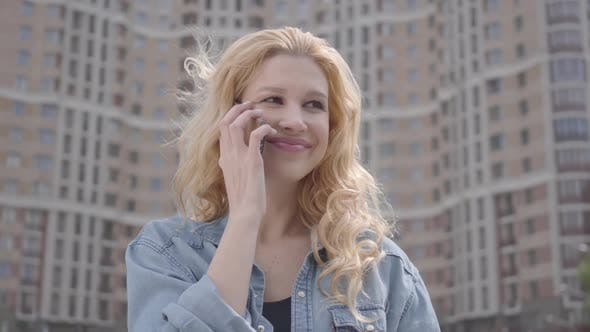 Thumbnail for Close-up Face of Pretty Smiling Confident Blond Woman Talking By Cellphone in Front of Skyscraper