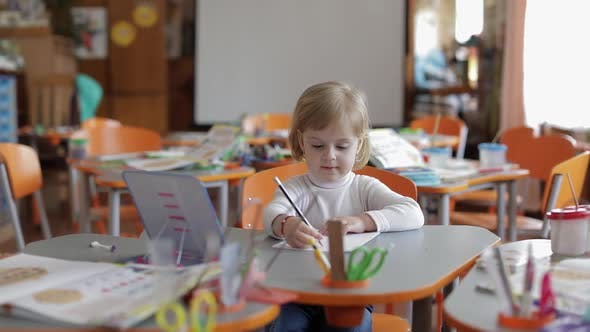 Thumbnail for Girl Drawing at the Table in Classroom