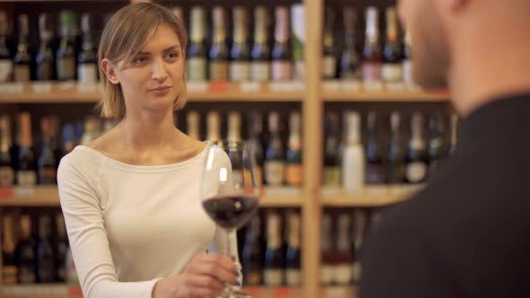 Thumbnail for Girl in a Wine Shop Offers a Glass of Wine To a Guy