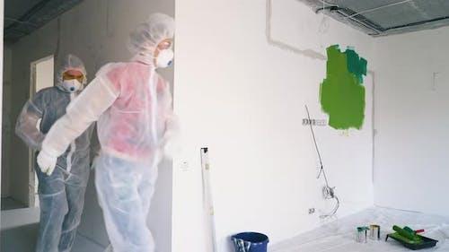 Joyful Couple in Protective Suits Respirators Enters Room