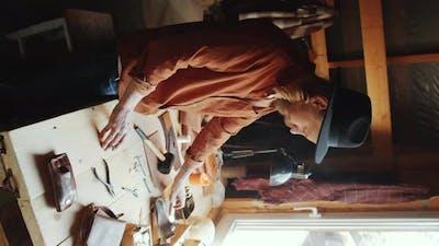 Craftsman Preparing Tools in Leather Workshop