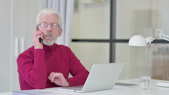 Thumbnail for Old Man with Laptop Talking on Smartphone