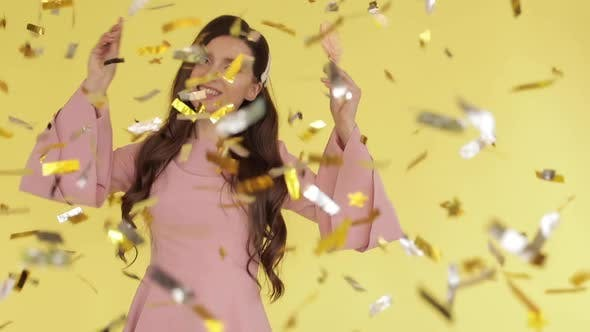 Thumbnail for Beautiful Brunette Girl in Pink Dress Dancing with Candies Under Confetti