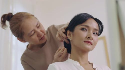 Professional Hairdresser Working With Asian Bride On Wedding Day.