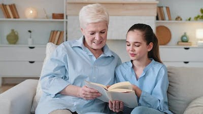 Smart Girl Granddaughter Reading with Grandma at Home