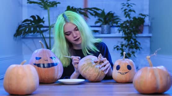 Preparation of Halloween Party, Young Teenager Girl with Scary Witch Make-up Drawing on Pumpkins