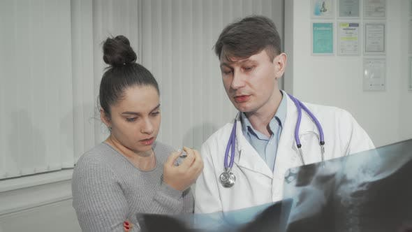 Doctor Explaining Xray Scanning Results to His Female Patient