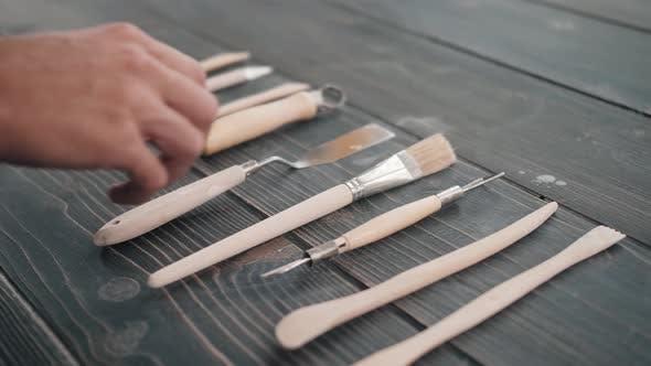 Erhöhte Ansicht einer Auswahl von Keramikwerkzeugen auf einem Brett in einer Werkstatt Potter Equipment