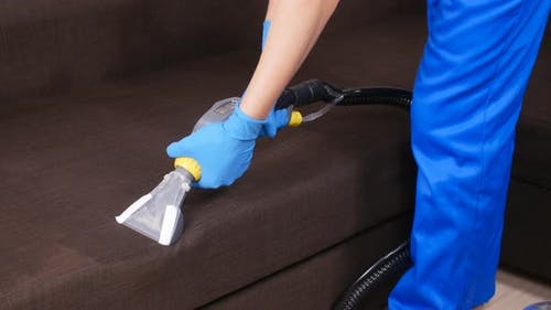 Cleanliness Concept. Dry Cleaning Worker Removing Dirt From Upholstered Furniture