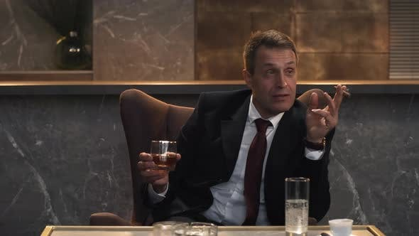 Cover Image for Caucasian Male Executive with Drink and Cigar Talking at Meeting