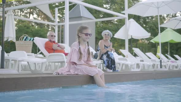 Thumbnail for Mature Couple Lying on Sunbeds Near the Pool on the Background
