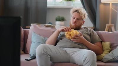 Obese Man Eating Chips and Watching TV at Home