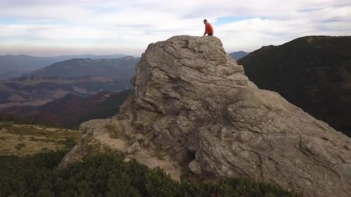 Aerial view of a hiker man climbing big rock in mountains