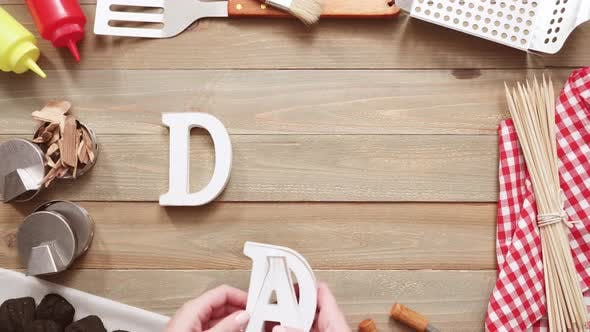 Dad sign for Father's Day with grilling tools on wood background.