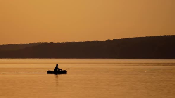 Silhouette of fisherman in boat. Fishing on a lake from the boat at sunset