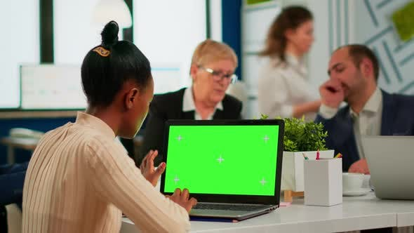 African Manager Woman Sitting at Conference Desk Looking at Laptop with Green Screen